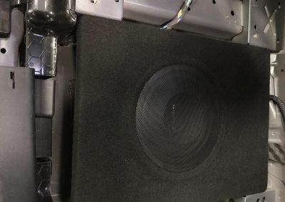 Actieve subwoofer onder stoel gemonteerd in Landrover Evoque